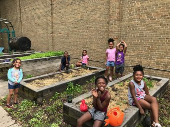 A group of smiling children play in raised garden beds